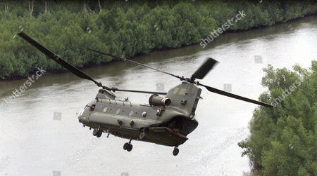 Sierra Leone A Raf Chinook Hugs The Treetops As It Swoops To Follow The River Near Its Base At Lungi.
